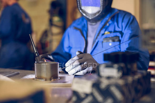 Factory worker wearing protective clothing, soldering manufacturing machine part — Stock Photo