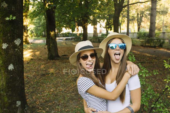 Portrait de deux jeunes amies en chapeaux trilby sortant des langues dans le parc — Photo de stock