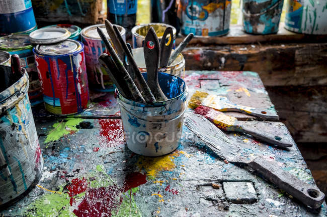 Paint brushes and pots of paints on workshop table — Stock Photo