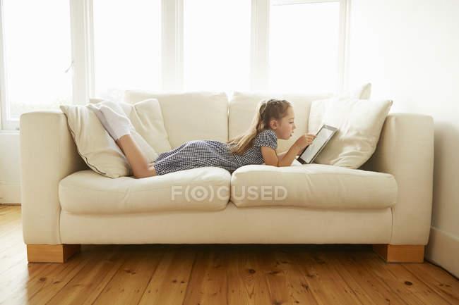 Девочка лежит на диване с цифровым планшетом — стоковое фото