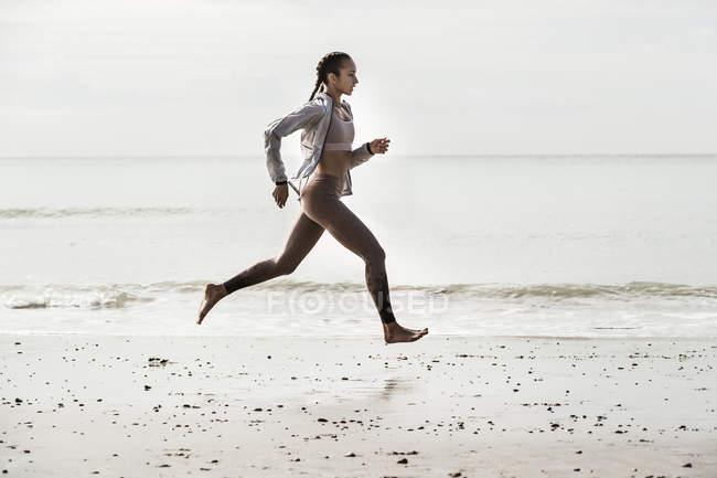 Вид збоку молода жінка бігун біг босоніж, вздовж елегантній на пляжі — стокове фото