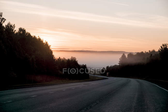 Road disappearing around bend at sunset — Stock Photo