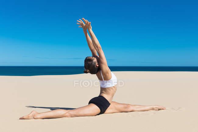 Frau am Strand mit Yogaposition erhobenen Armen — Stockfoto