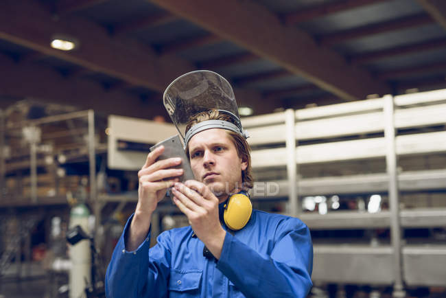 Factory worker wearing protective clothing, holding metal machine part — Stock Photo