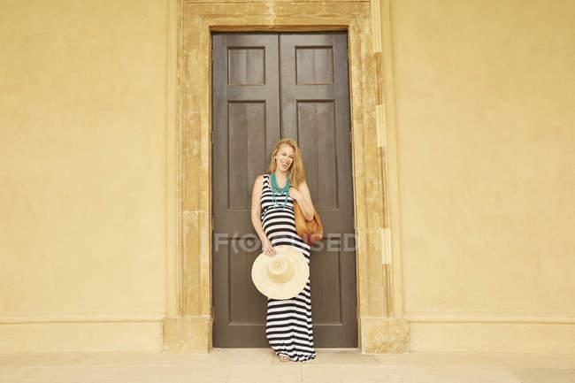 Беременная женщина позирует перед большими двойными дверями — стоковое фото