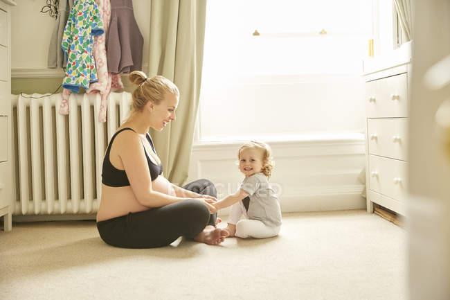 Donna incinta e figlia seduta al piano in camera da letto — Foto stock