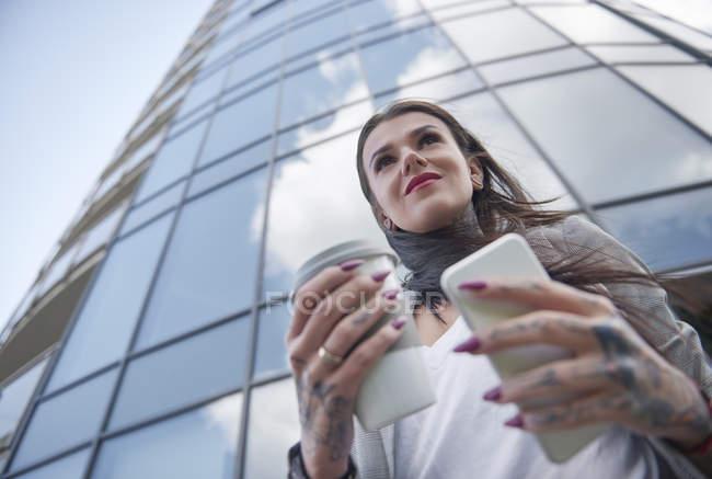 Empresária perto de prédio de escritórios segurando xícara de café e smartphone — Fotografia de Stock