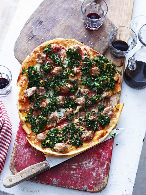 Sliced Italian sausage pizza on serving board, top view — Stock Photo