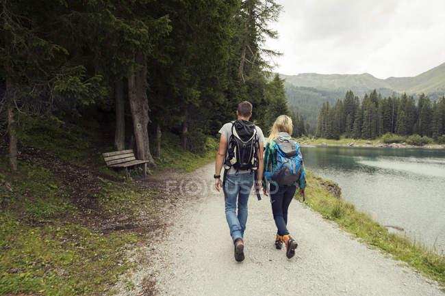 Rear view of couple hiking by lake, Tirol, Steiermark, Austria, Europe — Stock Photo