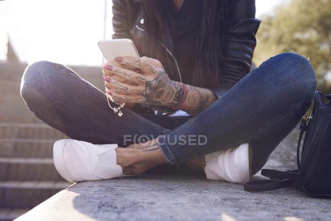 Молодая женщина сидит на стене, используя смартфон, татуировки на руке, низкий раздел — стоковое фото