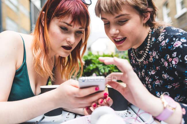 Dos mujeres jóvenes en la mesa del café de la acera mirando el teléfono inteligente - foto de stock