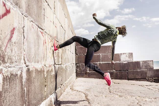 Vue latérale du jeune homme courant sur le mur — Photo de stock