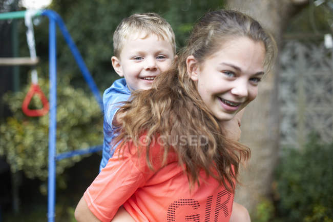 Portrait of young girl carrying young brother on back — Stock Photo