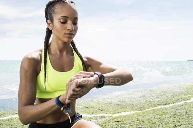 Jeune femme en vêtements de sport regardant traqueur d'activité — Photo de stock