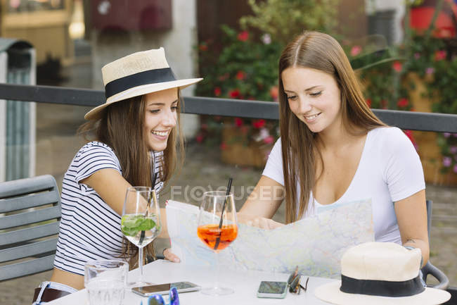 Two young female friends looking at map at sidewalk cafe — Stock Photo