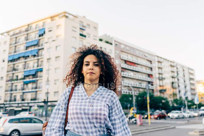 Donna in strada con blocco residenziale sullo sfondo, Milano, Italia — Foto stock