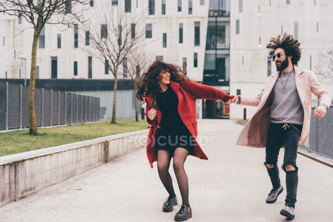 Young couple outdoors, running hand in hand — Stock Photo