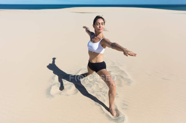 Woman on beach stretching in yoga position — Stock Photo