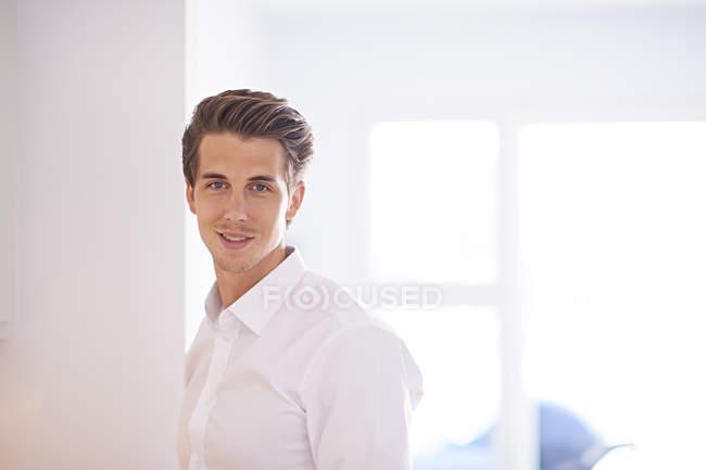 Porträt eines Mannes im weißen Hemd, der in die Kamera lächelt — Stockfoto