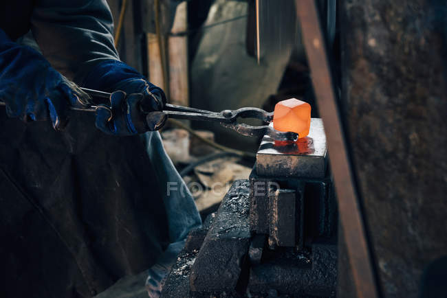Gloved hands of blacksmith using tongs for red hot metal — Stock Photo
