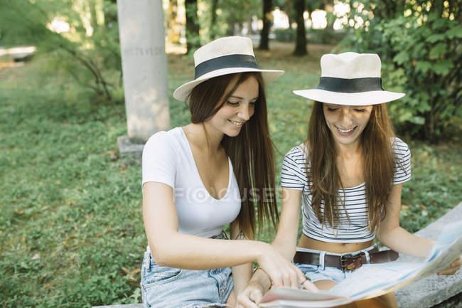 Две молодые подружки сидят на скамейке и указывают на карту в парке. — стоковое фото