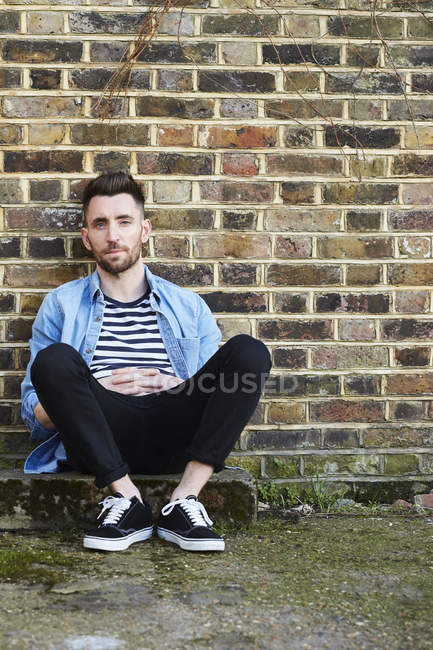 Portrait of young adult man sitting in front of brick wall — Stock Photo