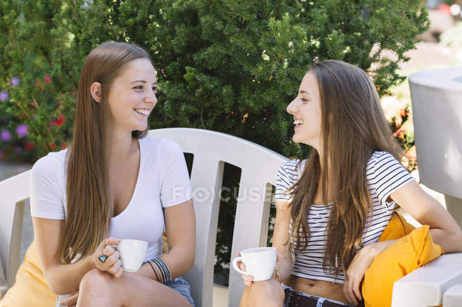 Two young female friends chatting over coffee at sidewalk cafe — Stock Photo