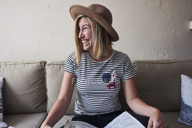 Frau sitzt auf dem Sofa, Zeitung auf Schoß, Wegsehen, lachen — Stockfoto