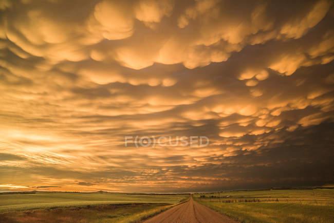 Nuvens de mamíferos acima da estrada rural durante o pôr do sol, Dickinson, Dakota do Norte, EUA — Fotografia de Stock