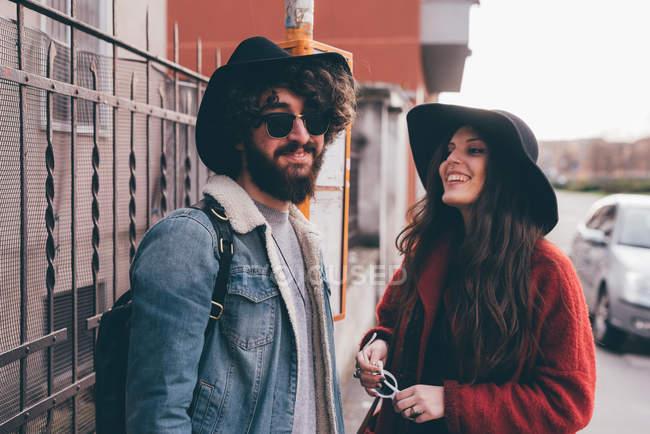 Молодая пара, стоящая на автобусной остановке, смеющаяся — стоковое фото