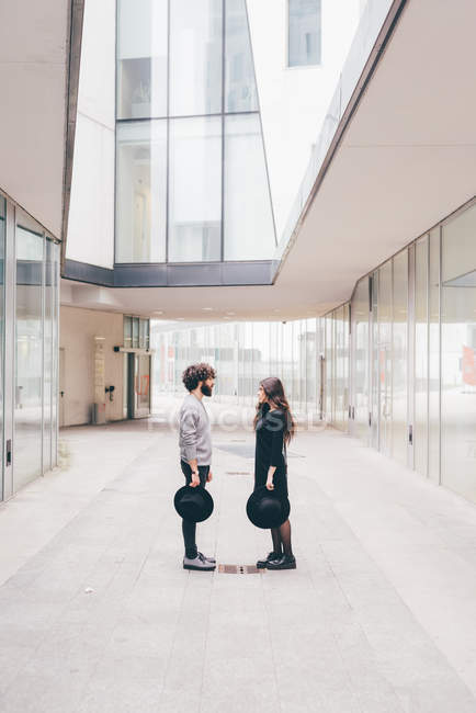 Young man and woman standing face to face in urban environment — Stock Photo