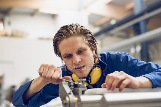 Factory worker wearing protective clothing, adjusting machine part — Stock Photo