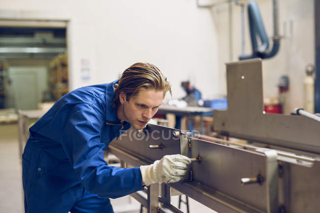 Factory worker wearing protective clothing, adjusting manufacturing machine part — Stock Photo