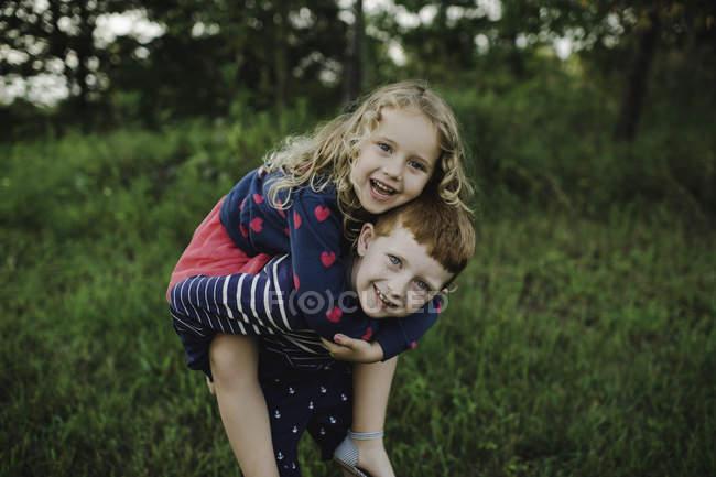 Retrato de niño dando hermana un piggyback en el campo - foto de stock