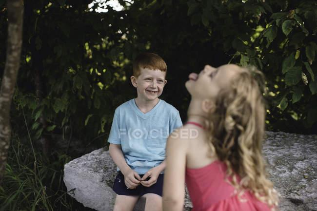 Ragazza sporge la lingua al fratello seduto su roccia — Foto stock
