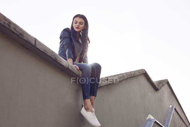 Молодая женщина сидит на крыше, вид с низкого угла — стоковое фото
