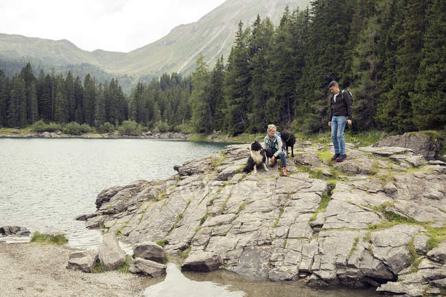 Couple with dogs hiking by lake, Tirol, Steiermark, Austria, Europe — Stock Photo