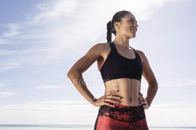 Jeune coureuse sur la plage contre le ciel bleu — Photo de stock