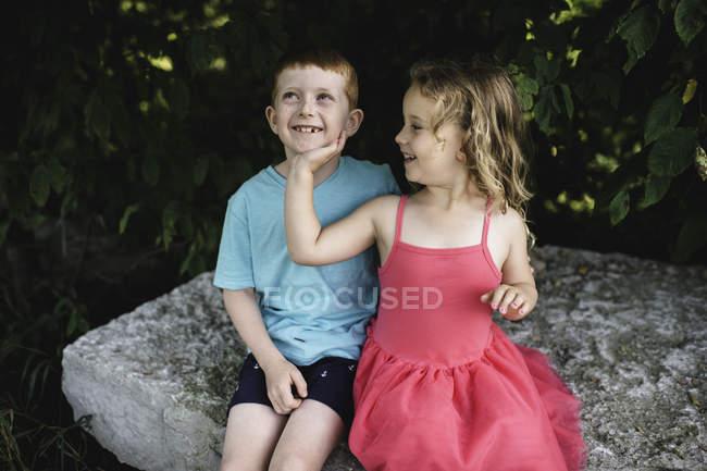 Jeune fille à la main sur le menton de frère, assis sur rocher — Photo de stock