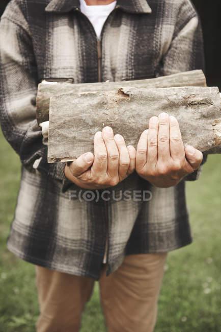 Mature man outdoors holding firewood — Stock Photo