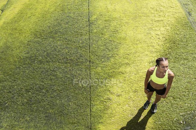 Mujer joven en ropa deportiva de pie sobre algas marinas - foto de stock