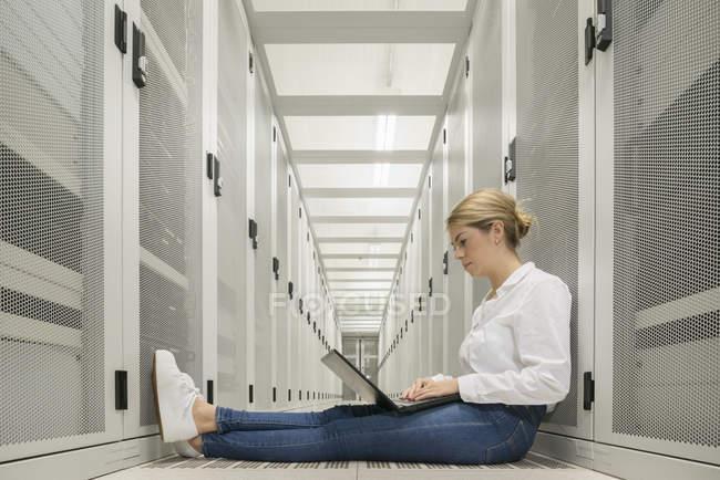 Mujer joven en el centro de datos sentado en el suelo con el ordenador portátil - foto de stock