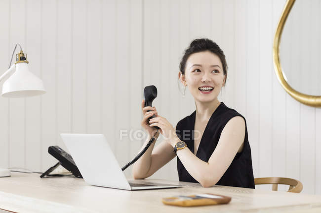 Young woman at desk with telephone handset — Stock Photo