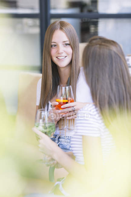 Two young female friends chatting over cocktails at sidewalk cafe — Stock Photo