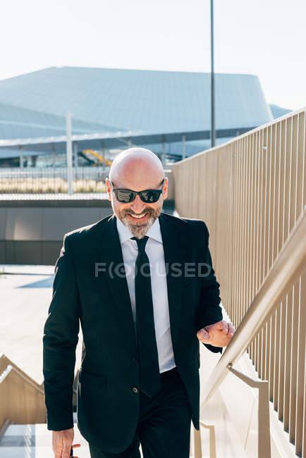 Portrait d'un homme d'affaires mature marchant sur les marches — Photo de stock