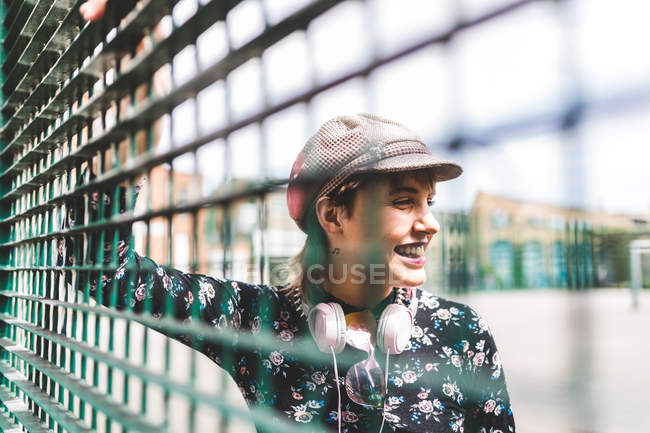 Retro styled young woman in baker boy hat behind wires fence — Stock Photo