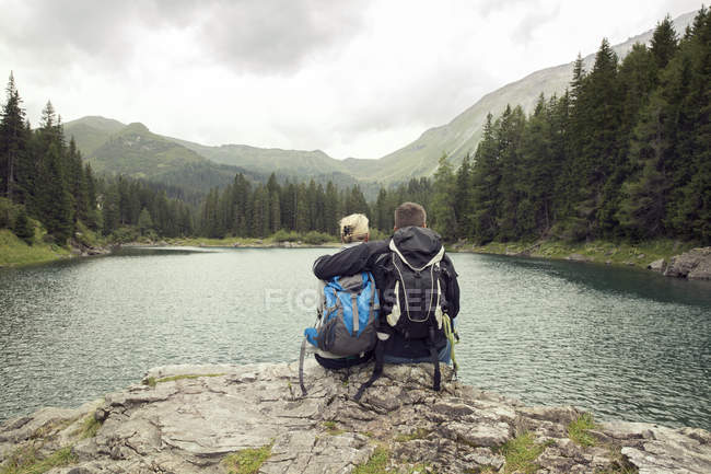 Вид сзади пара походов, сидя у озера, Tirol, Steiermark, Австрии, Европе — стоковое фото