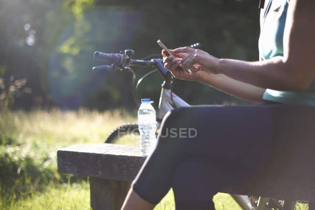 Вид сбоку женской велосипедист с помощью мобильного телефона — стоковое фото