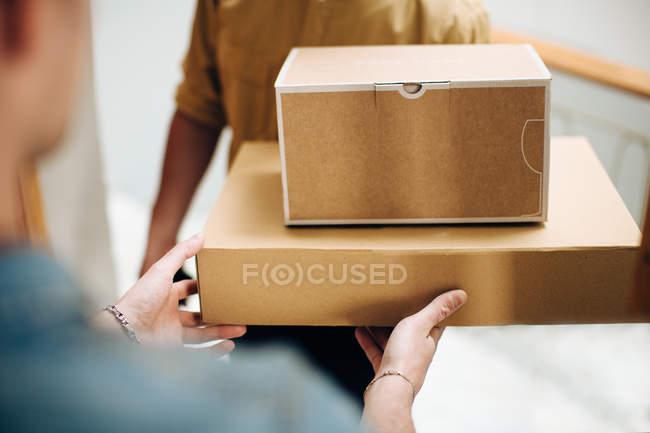 Людина відкриття двері для кур'єрської доставки посилок — стокове фото