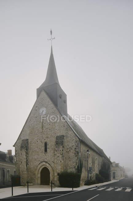 Iglesia en Meigne-le-Vicomte pueblo en la mañana brumosa, Valle del Loira, Francia - foto de stock